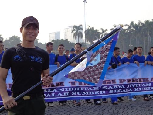 Taruna Sabri semester II Teknologi Pengolahan Sumber Daya Perairan memegang bendera pandu, sekaligus memandu pasukan Jalan Sehat
